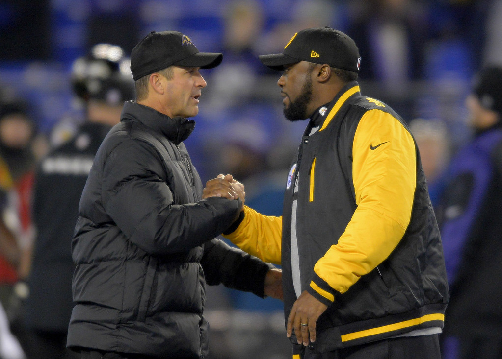 Description of . Baltimore Ravens head coach John Harbaugh (L) and Pittsburgh Steelers head coach Mike Tomlin shake hands after chatting at mid field before  their game in Baltimore on Thursday, November 28, 2013. (Doug Kapustin/MCT)