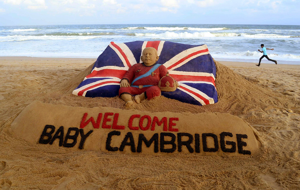 Description of . A boy runs past a sculpture created by Indian sand artist Sudarshan Pattnaik to mark the birth of Britain\'s royal baby, on a beach in Puri, located in the eastern Indian state of Odisha, July 23, 2013.  REUTERS/Stringer