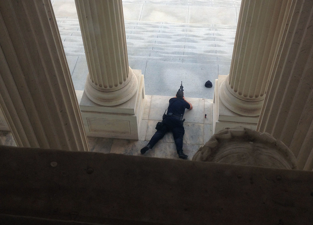 Description of . A U.S. Capitol police officer lies on the steps of the Senate with a gun drawn in response to a report of shots fired Thursday, Oct. 3, 2012. A police officer was reported injured after gunshots at the U.S. Capitol. They locked down the entire complex, at least temporarily derailing debate over how to end a government shutdown. (AP Photo/The Tampa Bay Times, Alex Leary)