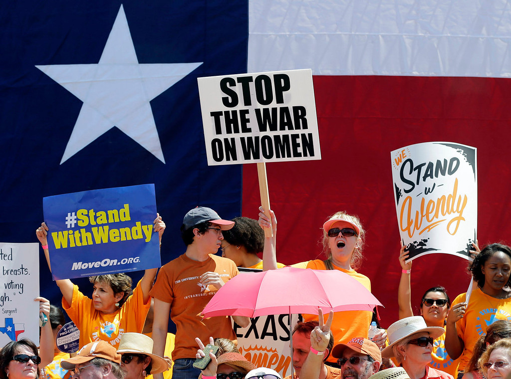 Description of . Pro-choice supporters cheer during a rally outside the Texas capitol, Monday, July 1, 2013, in Austin, Texas. The Texas Senate has convened for a new 30-day special session to take up a contentious abortion restrictions bill and other issues. (AP Photo/Eric Gay)