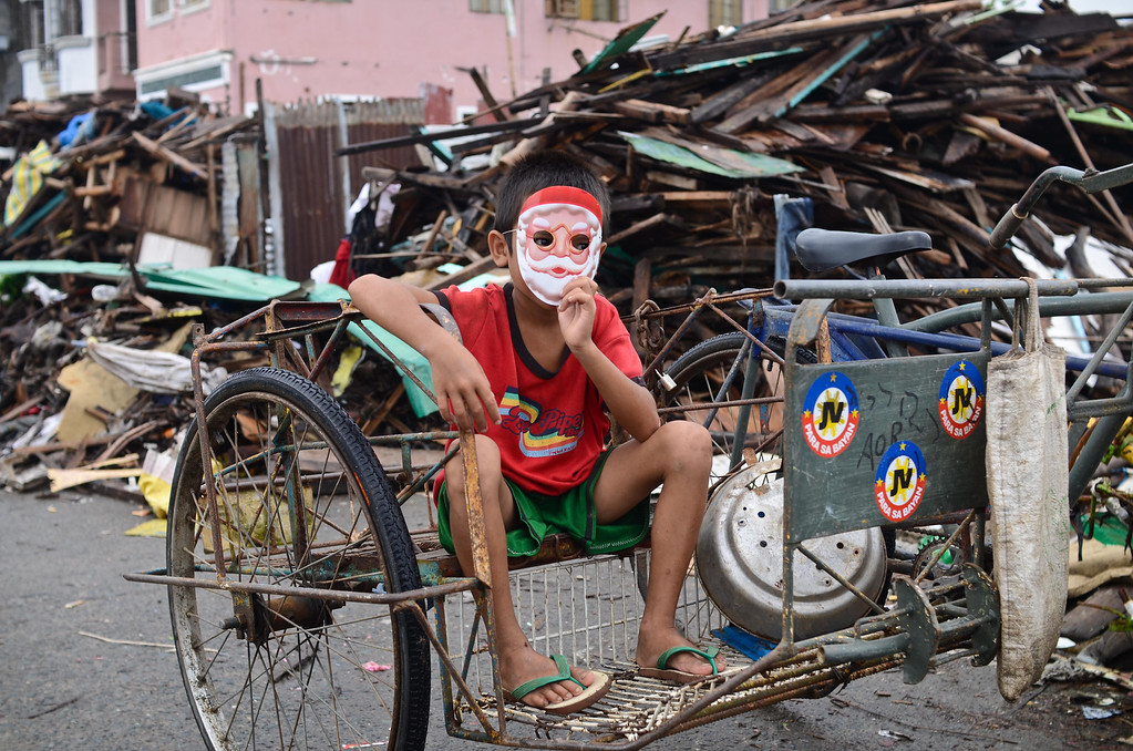 Description of . A boy with a Santa Claus mask sits on a pedicab on Christmas Eve on December 24, 2013 in Tacloban, Leyte, Philippines. Haiyan has been described as one of the most powerful typhoons ever to hit land, leaving thousands dead and hundreds of thousands homeless. Countries all over the world have pledged relief aid to help support those affected by the typhoon. With Christianity being the predominant religion in Philippines, the people of Tacloban will try to find a way to celebrate Christmas despite the incredibly difficult circumstances.  (Photo by Dondi Tawatao/Getty Images)