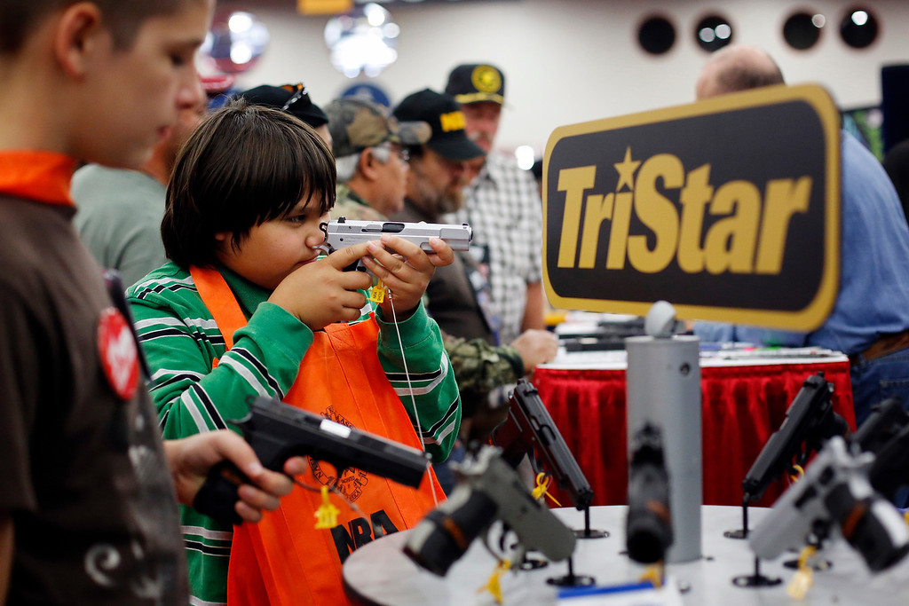 Description of . Brothers, 10-year-old Kayden La, center. and 13-year-old Jacob La, left, inspect pistols at a booth, during the NRA Annual Meeting of Members at the National Rifle Association's 142 Annual Meetings and Exhibits in the George R. Brown Convention Center Saturday, May 4, 2013, in Houston. National Rifle Association leaders told members Saturday that the fight against gun control legislation is far from over, with battles yet to come in Congress and next year's midterm elections, but they vowed that none in the organization will ever have to surrender their weapons. (AP Photo/Houston Chronicle, Todd Spoth)