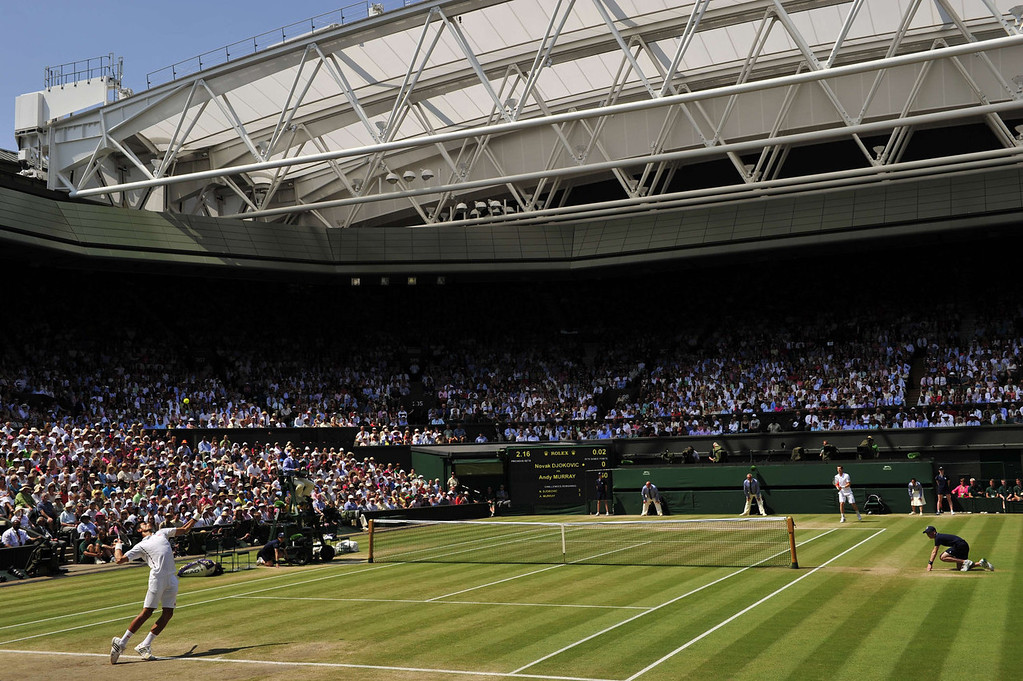 Description of . Serbia's Novak Djokovic (L) serves against Britain's Andy Murray (R) during the men's singles final on day thirteen of the 2013 Wimbledon Championships tennis tournament at the All England Club in Wimbledon, southwest London, on July 7, 2013. GLYN KIRK/AFP/Getty Images