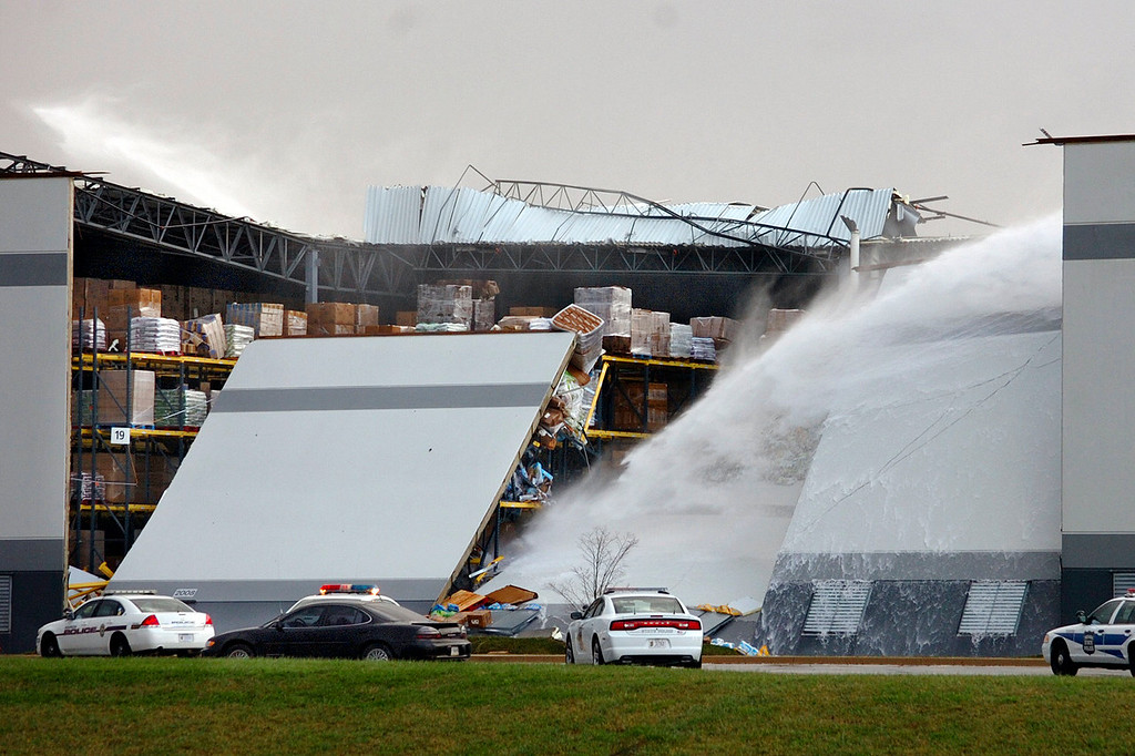 Description of . Water shoots from broken pipes after part of a wall and roof collapsed in high winds at the Dollar General distribution center at Ind. 18 and Grant County Road 600 East east of Marion, Ind., on Sunday, Nov. 17, 2013.  (AP Photo/Chronicle-Tribune, Jeff Morehead)