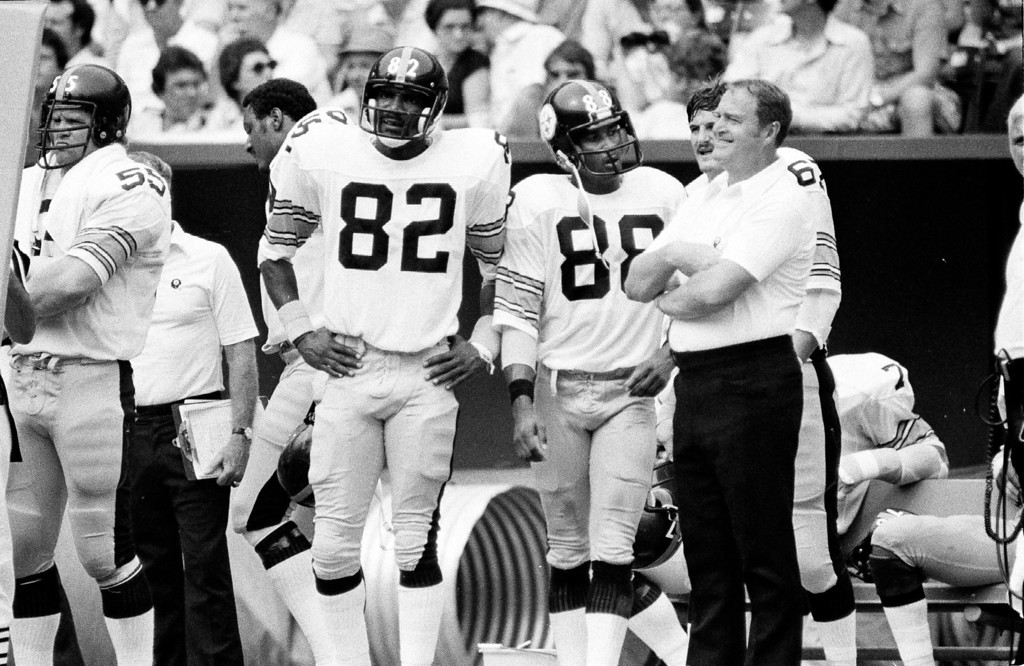 Description of . Pittsburgh Steelers head coach Chuck Noll has a smile as he stood with arms folded on sidelines in a Pittsburgh Steelers game in 1978 with John Stallworth (82) and Lynn Swann (88). (AP Photo)