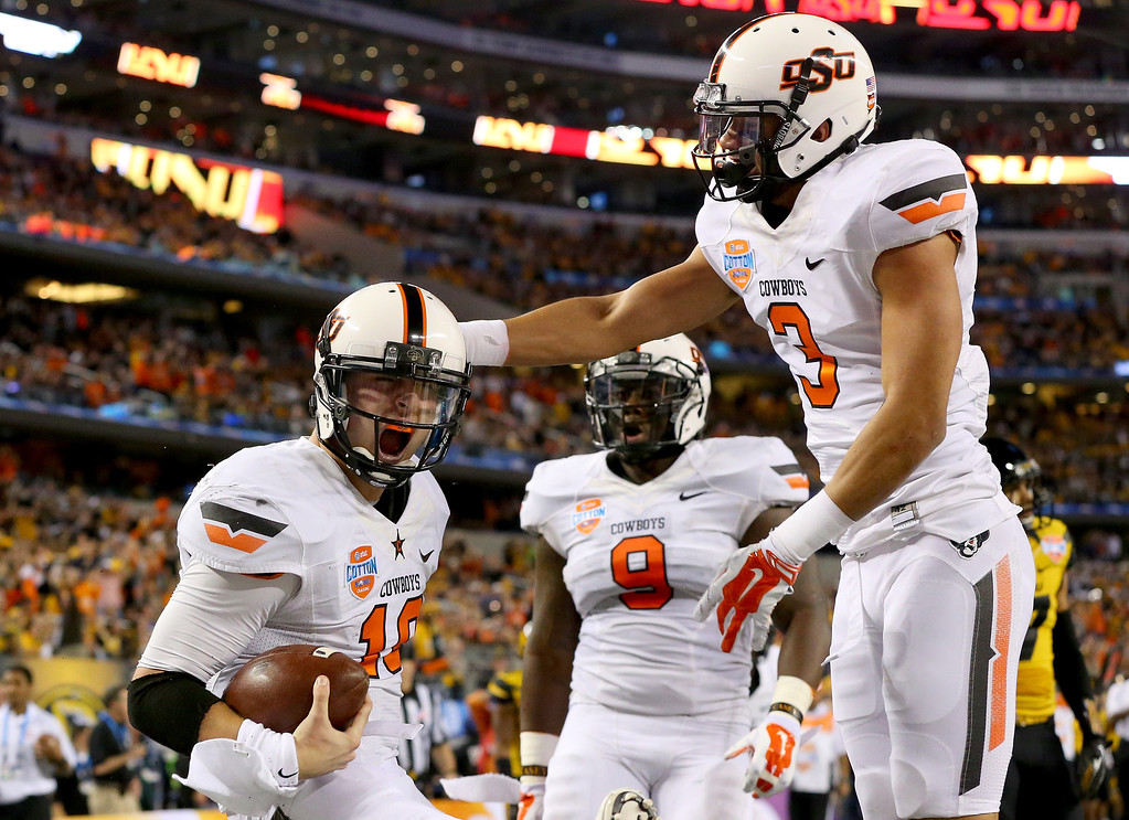 Description of . ARLINGTON, TX - JANUARY 03:  Quarterback Clint Chelf #10 of the Oklahoma State Cowboys celebrates with Marcell Ateman #3 after Chelf rushes for a 23-yard touchdown in the fourth quarter against the Missouri Tigers during the AT&T Cotton Bowl on January 3, 2014 in Arlington, Texas.  (Photo by Ronald Martinez/Getty Images)
