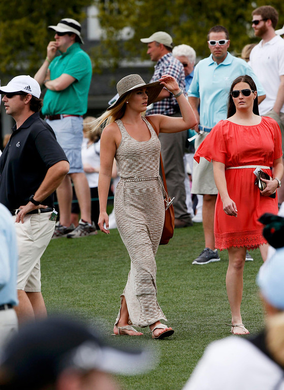 Description of . Skier Lindsey Vonn (C), girlfriend of Tiger Woods, watches play with physical therapist Lindsay Winninger (R) during first round play in the 2013 Masters golf tournament at the Augusta National Golf Club in Augusta, Georgia, April 11, 2013.      REUTERS/Mike Segar