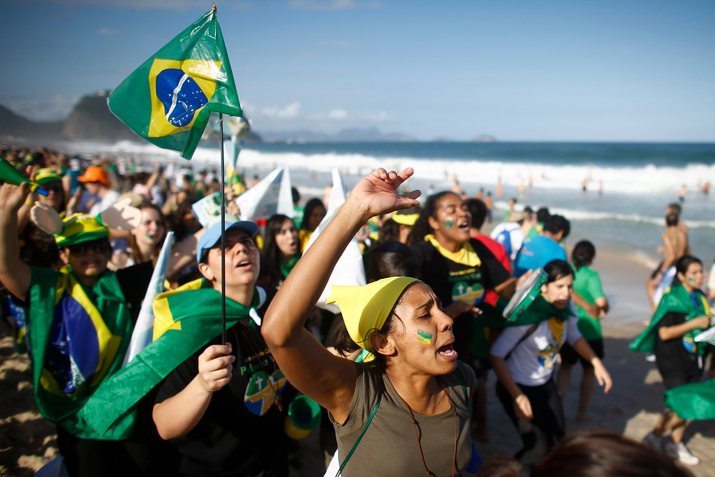 Description of . Pilgrims carrying a Brazilian flag sing on Copacabana beach in Rio de Janeiro, Brazil, Saturday, July 27, 2013. Pope Francis will preside over an evening vigil service on Copacabana beach that is expected to draw more than 1 million young people. (AP Photo/Victor R. Caivano)