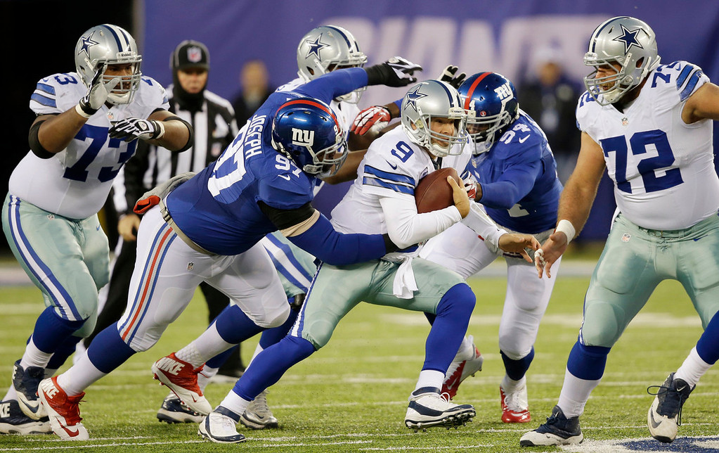 Description of . Dallas Cowboys quarterback Tony Romo (9) is tackled by New York Giants defensive tackle Linval Joseph (97) during the first half of an NFL football game Sunday, Nov. 24, 2013, in East Rutherford, N.J. (AP Photo/Seth Wenig)