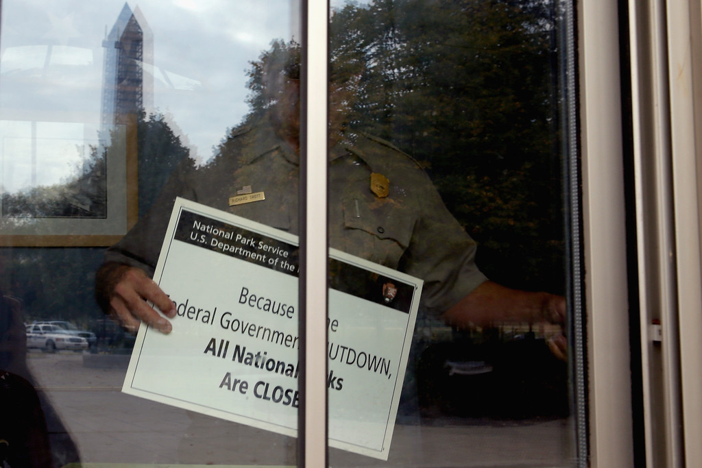 Description of . U.S. Park Service employee puts a closed sign in the window of the World War II Memorial ticket office on the National Mall October 1, 2013 in Washington, DC.  (Photo by Chip Somodevilla/Getty Images)