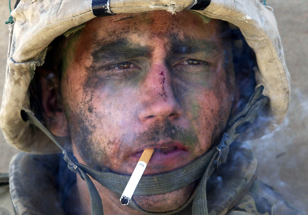 . Marine Lance Cpl. James Blake Miller, 20, of Kentucky, a member of Charlie Company of the U.S. Marines First Division, Eighth regiment, smokes a cigarette in Fallujah, Iraq, on Nov. 9, 2004. (AP Photo/Los Angeles Times, Luis Sinco)