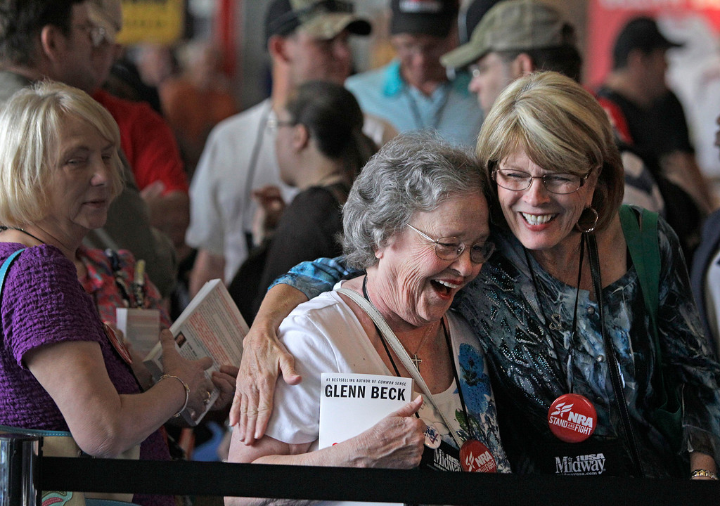 Description of . Eby Owen, center, of Dunedin, Fla., and Debbie Brinson, right, of San Antonio share a hug as they wait in line for the Glenn Beck book signing event during the NRA convention at the George R. Brown Convention Center  Saturday, May 4, 2013, in Houston. National Rifle Association leaders told members Saturday that the fight against gun control legislation is far from over, with battles yet to come in Congress and next year's midterm elections, but they vowed that none in the organization will ever have to surrender their weapons. (AP Photo/Houston Chronicle,  Melissa Phillip)