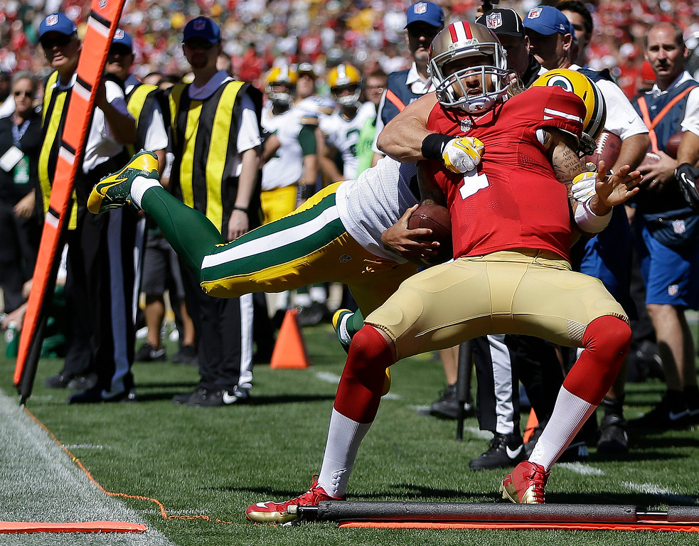 Description of . San Francisco 49ers quarterback Colin Kaepernick (7) is tackled as he is out of bounds by Green Bay Packers outside linebacker Clay Matthews during the second quarter of an NFL football game in San Francisco, Sunday, Sept. 8, 2013. (AP Photo/Ben Margot)