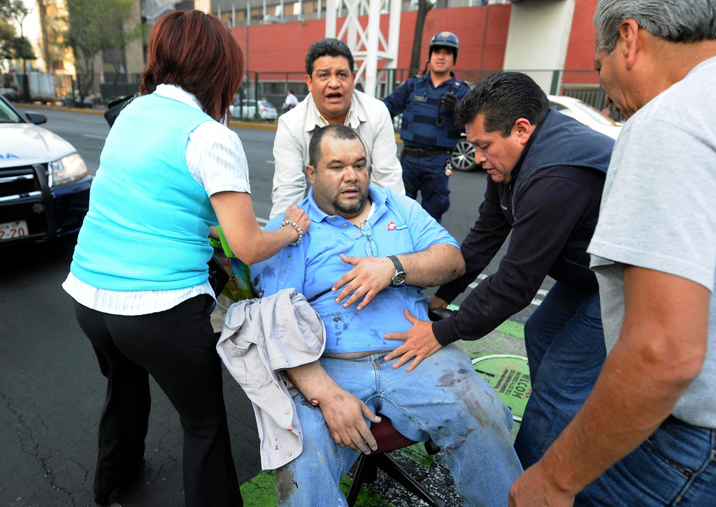 Description of . An injured man is being transported in an office chair outside the headquarters of state oil giant Pemex in Mexico City January 31, 2013. An explosion rocked the Mexico City headquarters of Pemex on Thursday, killing at least 14, injuring more than 100 others and causing extensive damage to the building. The blast, which media reports said was caused by machinery exploding, occurred in the basement, emergency officials said. REUTERS/Alejandro Dias