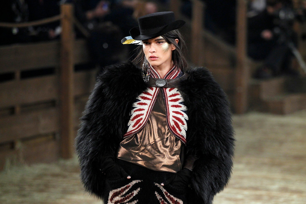 Description of . A model walks the runway at Chanel's Metiers d'Art fashion show, Tuesday, Dec. 10, 2013, in Dallas. For more than a decade, designer Karl Lagerfeld has picked a city linked to the house for the theme of the show staged each December to highlight the work of its artisans. Fashion house founder Gabrielle
