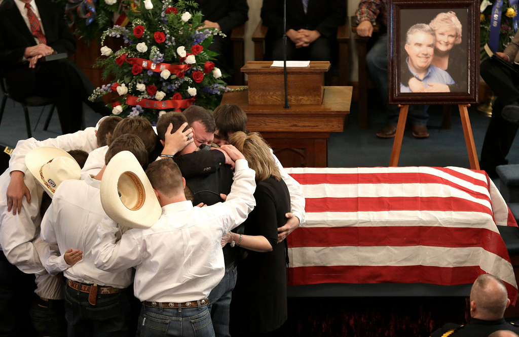Description of . The family of Kaufman County District Attorney Mike McLelland and his wife, Cynthia, comfort each other during their funeral services at  the First Baptist Church of Wortham Friday, April 5, 2013, in Wortham, Texas.  The couple was found shot to death in their house near Forney, about 20 miles east of Dallas.  (AP Photo/LM Otero)