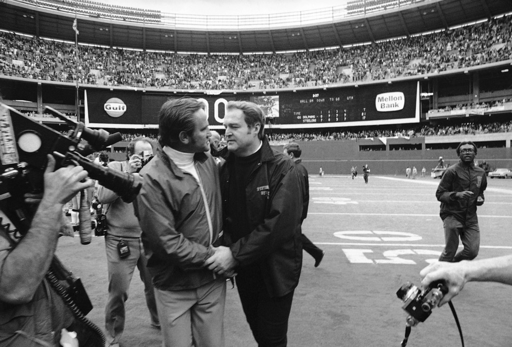 Description of . Miami Dolphins Coach Don Shula, left, embraces Pittsburgh Steelers Coach Chuck Noll on Jan. 1, 1972 in Pittsburgh, as the scoreboard behind them tells of the Dolphins 21-17 win over the Steelers for the American Football Conference championship. (AP Photo)