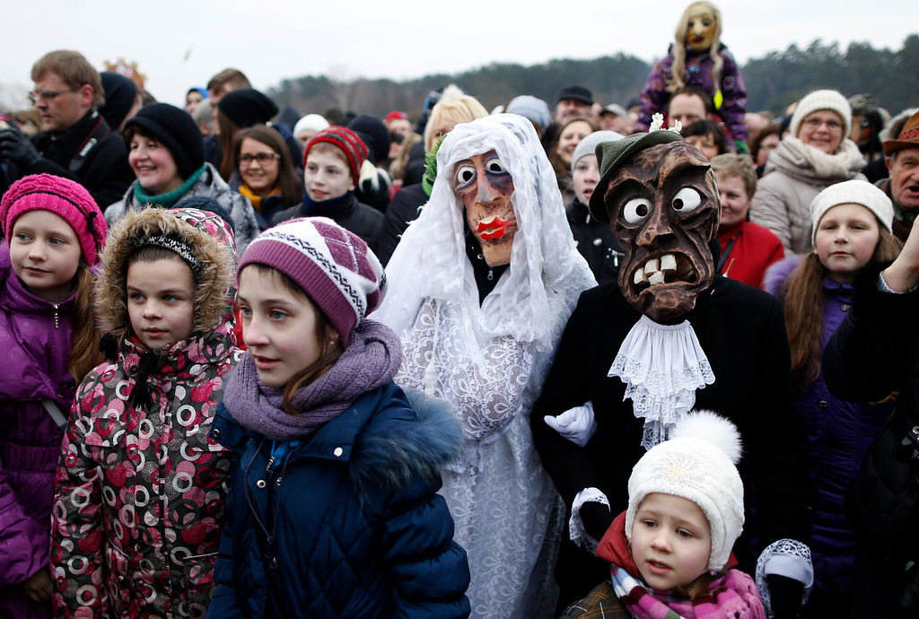 Description of . People gather watch an effigy of Lady Winter burning, with one couple wearing traditional carnival masks, during Shrovetide celebrations, in the Rumsiskes village, some 89 kilometers (56 miles) north of Vilnius, Lithuania, Saturday, March 1, 2014.  Shrovetide is a traditional Lithuanian holiday marking the end of winter. (AP Photo/Mindaugas Kulbis)
