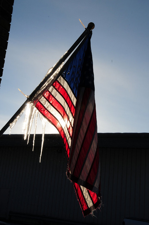 Description of . Cold temperatures are beginning to ease in Central Minnesota Wednesday, Dec. 26, 2012 after a Christmas holiday with temperatures dipping below zero. An American flag posted on the National Tire and Battery Store in Baxter, Minn. happened to be located near the melting snow on the roof forming icicles. (AP Photo/Brainerd Dispatch, Steve Kohls)