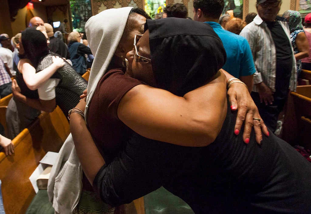Description of . Worshippers at the Middle Collegiate Church wearing hoodies hug during prayer services in support of slain teenager Trayvon Martin in response to the acquittal of George Zimmerman in his trial in New York, July 14, 2013. A Florida jury acquitted Zimmerman on Saturday for the shooting death of unarmed black teenager Martin, setting free a man who had become a polarizing figure in the national debate over racial profiling and self-defense laws. REUTERS/Keith Bedford