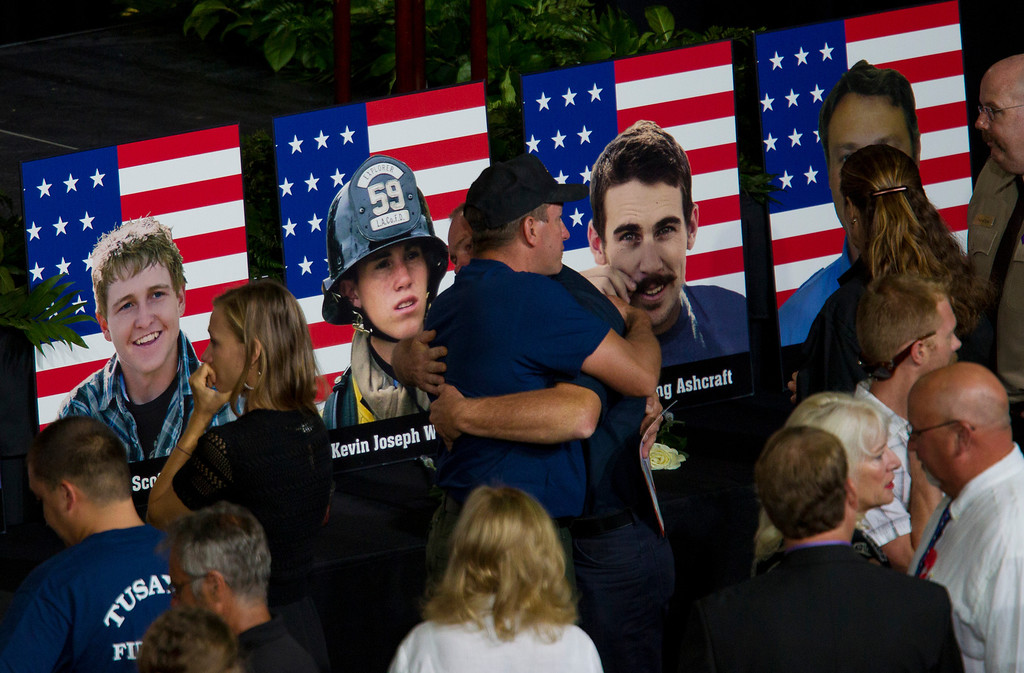 Description of . Photos of some of the 19 fallen firefighters line the front of the stage before a memorial service for the 19 fallen firefighters at Tim's Toyota Center in Prescott Valley, Ariz. on Tuesday, July 9, 2013.   Prescott's Granite Mountain Hotshots were overrun by smoke and fire while battling a blaze on a ridge in Yarnell, about 80 miles northwest of Phoenix on June 30, 2013.   (AP Photo/The Arizona Republic, Michael Chow, Pool)