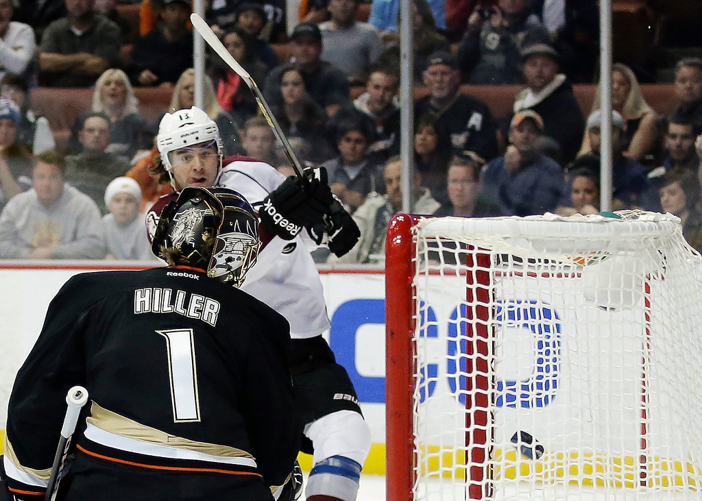 Description of . Anaheim Ducks goalie Jonas Hiller, left, watches Colorado Avalanche right wing P.A. Parenteau's shot go into the goal during the first period of an NHL hockey game in Anaheim, Calif., Sunday, Feb. 24, 2013. (AP Photo/Chris Carlson)