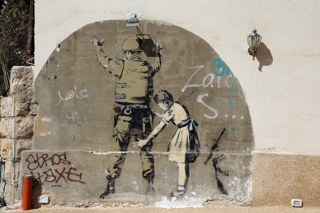 Description of . General views of a Banksy wall painting, on the apartheid wall near Bethlehem on June 16, 2013 in central West Bank.  (Photo by Ian Walton/Getty Images)