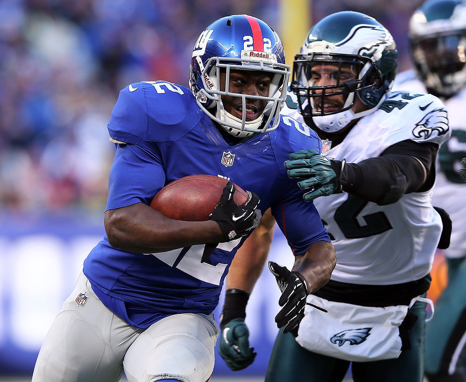 Description of . David Wilson #22 of the New York Giants carries the ball as  Kurt Coleman #42 of the Philadelphia Eagles defends at MetLife Stadium on December 30, 2012 in East Rutherford, New Jersey. The New York Giants defeated the Philadelphia Eagles 42-7.  (Photo by Elsa/Getty Images)