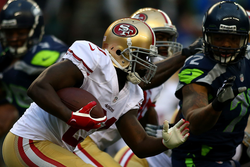 Description of . Frank Gore #21 of the San Francisco 49ers runs the ball against the Seattle Seahawks during their game at Qwest Field on September 15, 2013 in Seattle, Washington.  (Photo by Jonathan Ferrey/Getty Images)