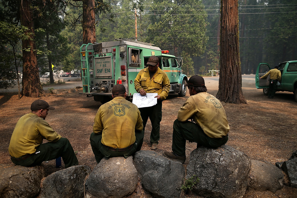 Description of . U.S. Forest Service firefighters take a break from battling the Rim Fire at Camp Mather on August 25, 2013 near Groveland, California.  (Photo by Justin Sullivan/Getty Images)