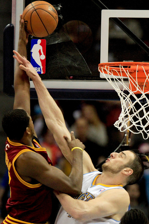 Description of . Denver Nuggets' Kosta Koufos, right, fouls Cleveland Cavaliers' Tristan Thompson left, who scored the basket during the first quarter of an NBA basketball game Friday, Jan. 11, 2013, in Denver. (AP Photo/Barry Gutierrez)