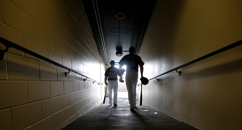 Description of . Atlanta Braves second baseman Dan Uggla (26) and first baseman Freddie Freeman (5) make their way to the field for a spring training baseball workout Wednesday, Feb. 20, 2013, in Kissimmee, Fla. (AP Photo/David J. Phillip)