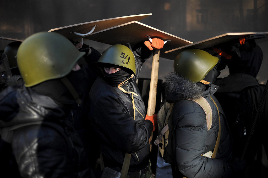 Description of . Anti-government protesters use wooden shields to protect themselves from the bullets fired by the riot police during an anti-government protest in downtown Kiev, Ukraine, 18 February 2014.  EPA/ALEXEY FURMAN