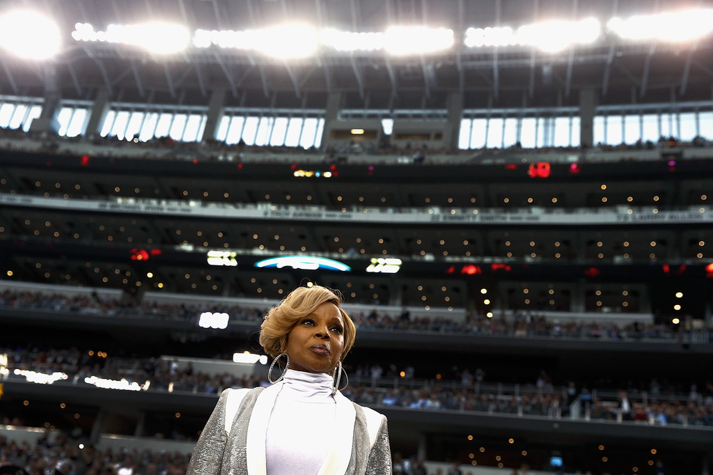 Description of . Singer Mary J. Blige prepares to sing the national anthem before a Thanksgiving Day game between the Oakland Raiders and the Dallas Cowboy at AT&T Stadium on November 28, 2013 in Arlington, Texas.  (Photo by Tom Pennington/Getty Images)