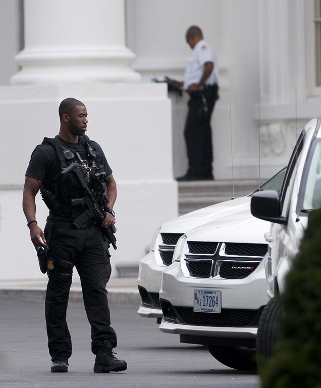 Description of . A member of the US Secret Service stands guard on the North Lawn of the White House in Washington, DC, October 3, 2013, following reports of a shooting at the US Capitol.