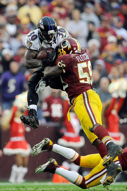 Description of . LANDOVER, MD - DECEMBER 09:  Bernard Pierce #30 of the Baltimore Ravens leaps to avoid the tackle of DeAngelo Hall #23 and London Fletcher #59 of the Washington Redskins during a game at FedExField on December 9, 2012 in Landover, Maryland.  (Photo by Patrick McDermott/Getty Images)