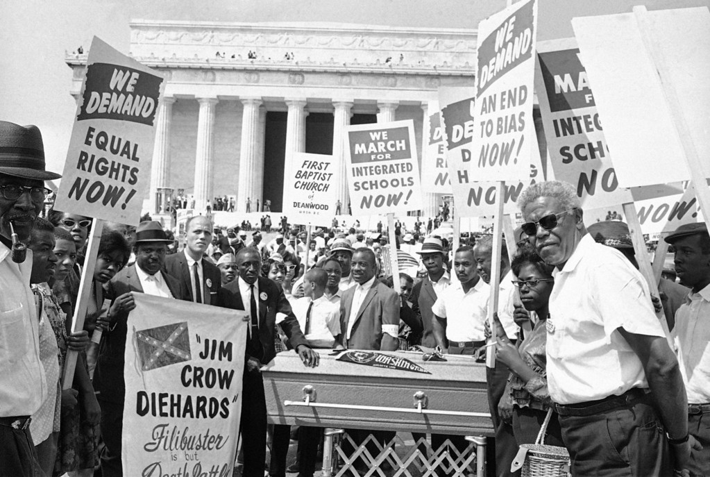 Description of . Group of demonstrators stand around casket at Lincoln Memorial in Washington, August 28, 1963. The group carried placards as they pushed the casket down Constitution Avenue during the March on Washington parade. (AP Photo)