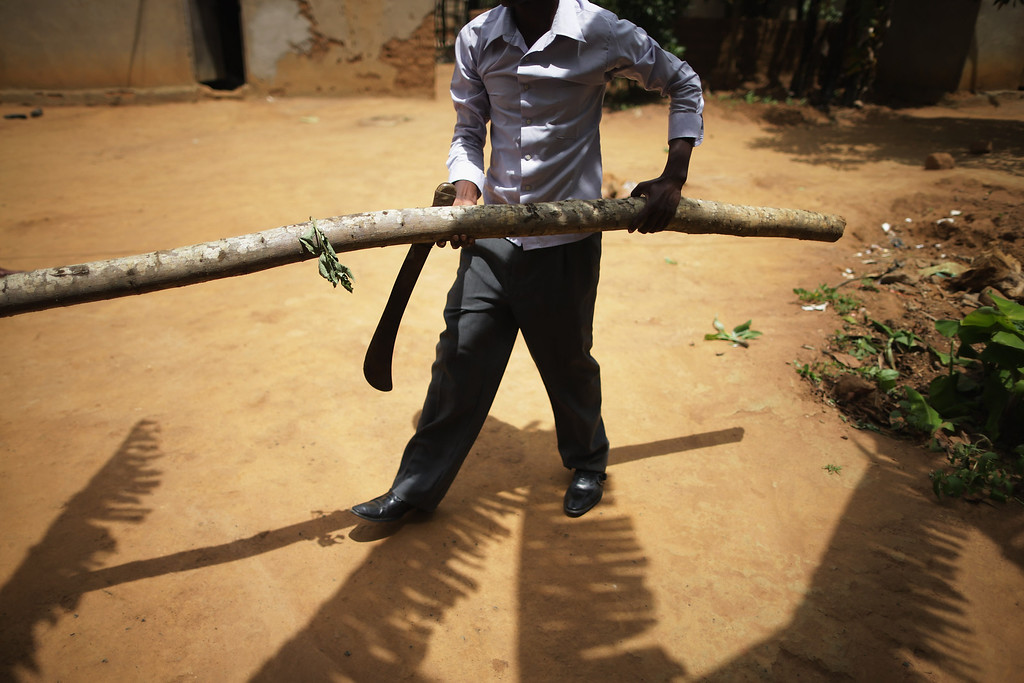 Description of . Silas Usengumuremyi clears a fallen tree at his home in a genocide