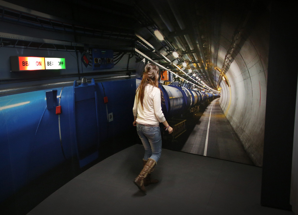 Description of . A visitor to the Science Museum walks towards a photograph of the workings of the Large Hadron Collider (LHC)  at the 'Collider' exhibition on November 12, 2013 in London, England.  (Photo by Peter Macdiarmid/Getty Images)