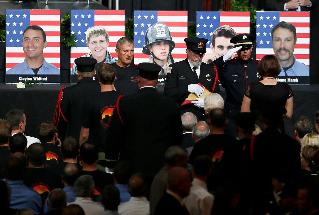 Description of . Grieving families are presented with the U.S. flag and the Pulaski tool at a memorial service for the fallen members of the Granite Mountain Hotshots, in Prescott Valley, Arizona July 9, 2013. REUTERS/Lucy Nicholson