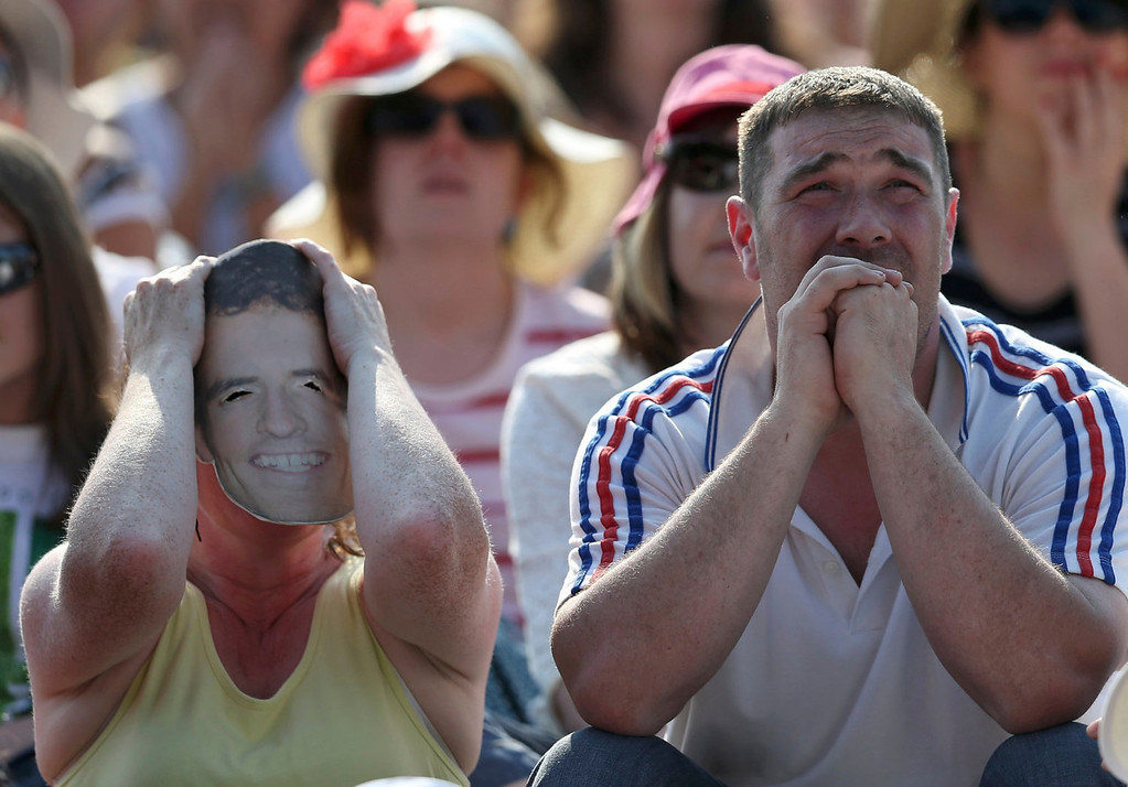 Description of . A fan wearing an Andy Murray mask watches the men's singles final tennis match between Andy Murray of Britain and Novak Djokovic of Serbia on the big screen at Murray Mound at the Wimbledon Tennis Championships, in London July 7, 2013.  REUTERS/Suzanne Plunkett