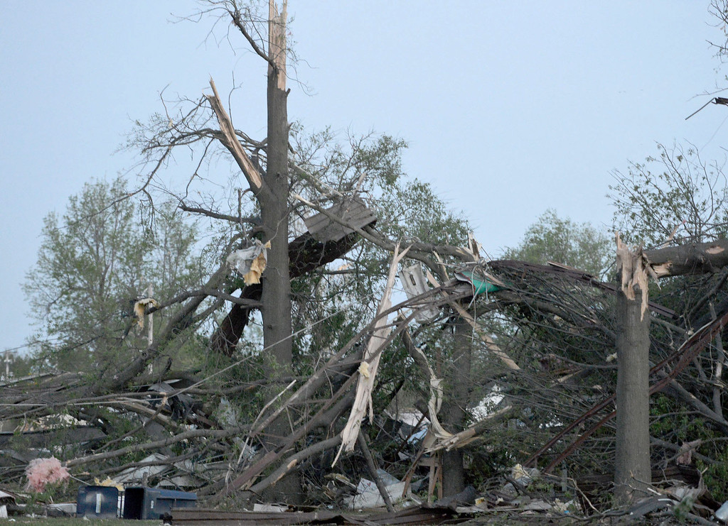 Description of . Twisted trees and power lines remain in a residential block near Military Avenue following  the tornado in Baxter Springs, Kan., Sunday, April 27, 2014.  A powerful storm system rumbled through the central and southern United States on Sunday, spawning a massive tornado that  carved through Little Rock's northern suburbs and another that hit Oklahoma and Kansas. (AP Photo/The Joplin Globe, Roger Nomer )