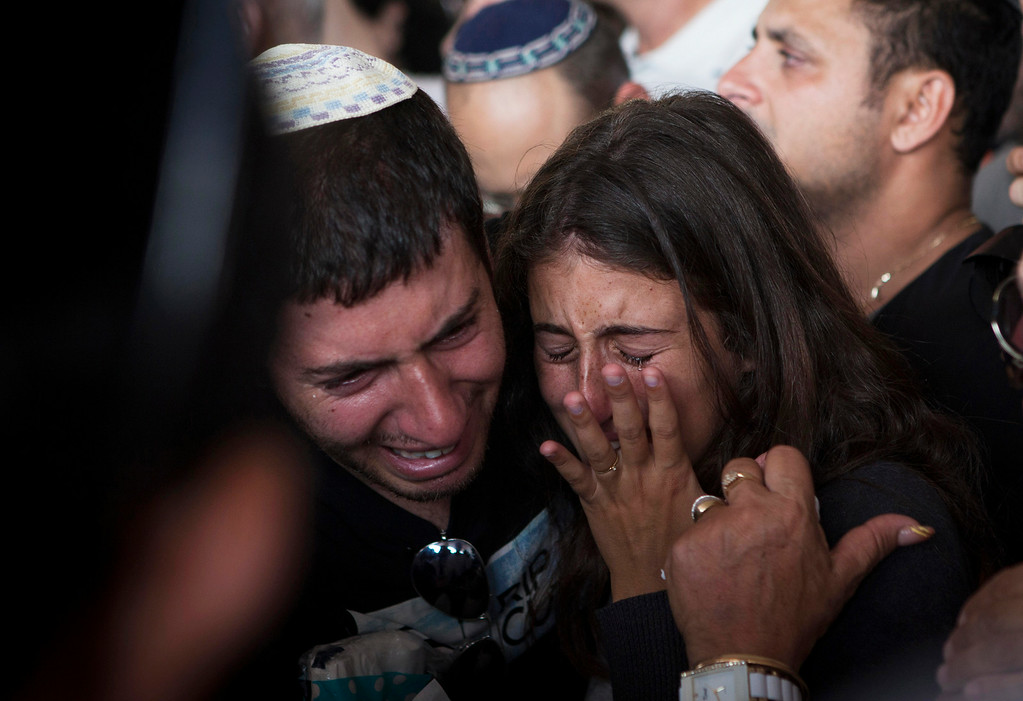 Description of . Relatives of Dror Chanin, 37, cry during his funeral in Yahud, Israel, Wednesday, July 16, 2014. Chanin was fatally wounded when a mortar exploded near the vehicle he was traveling in, spraying him with shrapnel. Israeli police said he was delivering food to soldiers near the Gaza border. (AP Photo/Dan Balilty)