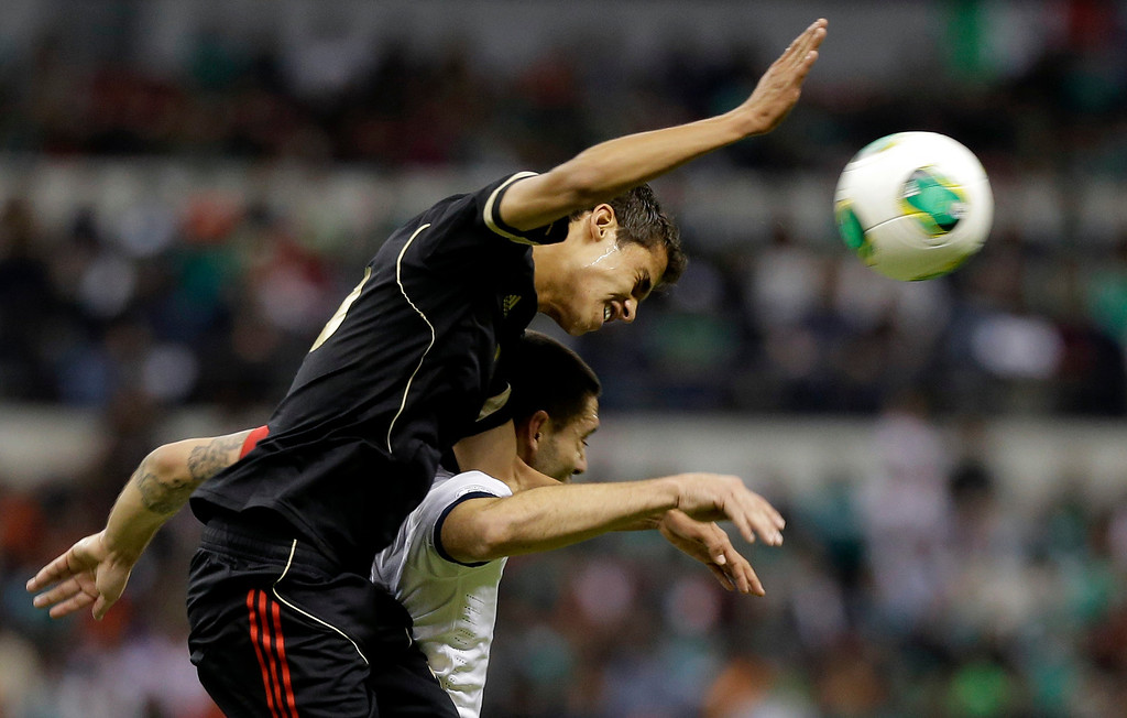 Description of . Mexico's Diego Reyes, left, and United States captain Clint Dempsey fight for the ball during a 2014 World Cup qualifying match at the Aztec stadium in Mexico City, Tuesday, March 26, 2013. (AP Photo/Eduardo Verdugo)