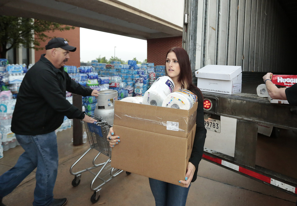 Description of . MOORE, OK -  MAY 23:   Cassadee Pope (R) helps unload donations at a distribution center setup for the victims at the First Baptist Church May 23, 2013  in Moore, Oklahoma. The tornado of at least EF4 strength and up to two miles wide touched down May 20 killing at least 24 people and leaving behind extensive damage to homes and businesses. U.S. President Barack Obama promised federal aid to supplement state and local recovery efforts.    (Photo by Brett Deering/Getty Images)