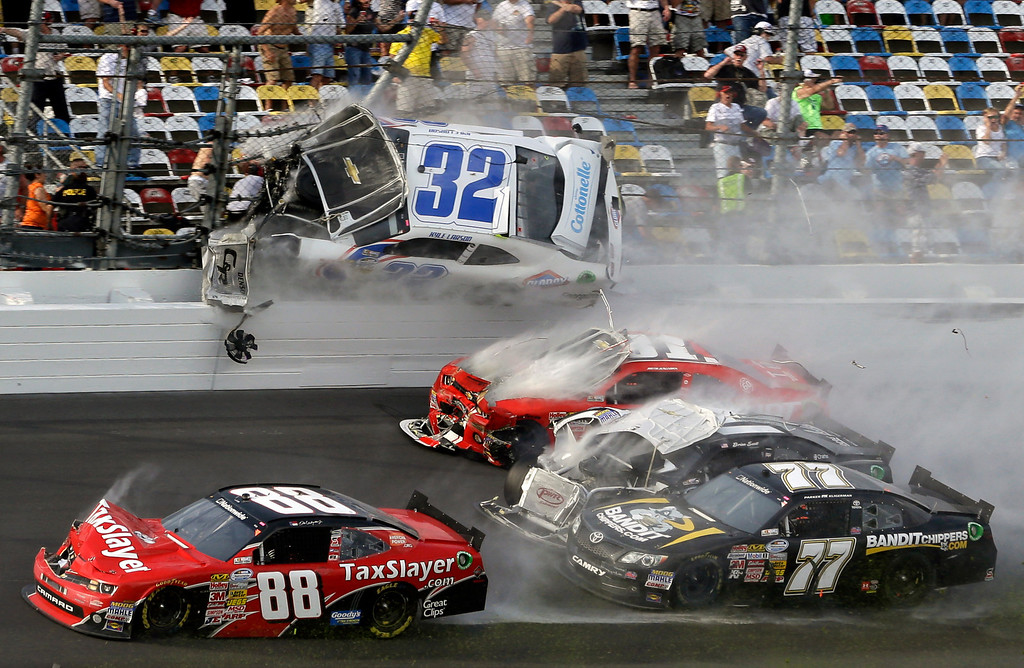 Description of . Kyle Larson (32) goes airborne into the catch fence in a multi-car crash including  Dale Earnhardt Jr. (88), Parker Kilgerman (77), Justin Allgaier (31) and Brian Scott (2) during the final lap of  the NASCAR Nationwide Series auto race at Daytona International Speedway, Saturday, Feb. 23, 2013, in Daytona Beach, Fla. (AP Photo/John Raoux)