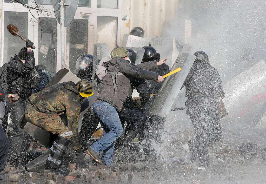 Description of . Anti-government protesters clash with riot police outside Ukraine's parliament in Kiev, Ukraine, Tuesday, Feb. 18, 2014. (AP Photo/Efrem Lukatsky)