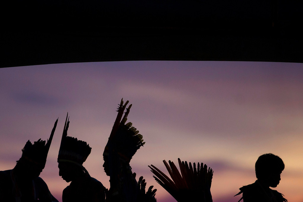 Description of . Indians are silhouetted against an early evening sky as the the sun begins to set during the indigenous games in Cuiaba, Brazil, Tuesday, Nov. 12, 2013.  (AP Photo/Felipe Dana)