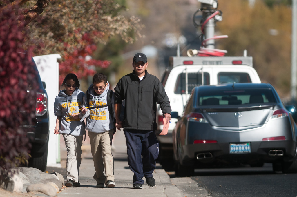 Description of . A parent escorts his children from Agnes Risley Elementary school following a shooting at nearby  Sparks Middle School October 21, 2013 in Sparks, Nevada.  (Photo by David Calvert/Getty Images)