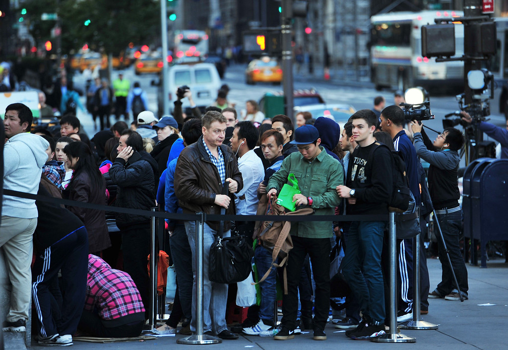 Description of . People waiting to buy the Apple iPhone 5 in line at the Apple Store on Fifth Avenue September 20, 2013 in New York. Some people waited as long as fifteen days in line outside the store to be the first to buy the phone. AFP PHOTO/Stan HONDA/AFP/Getty Images